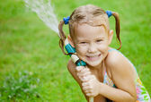 Happy girl pours water from a hose — Stock Photo