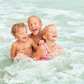 Happy kids playing on beach — Stock Photo