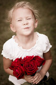 Happy child with a bouquet of red roses — Stock Photo