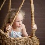 Sad girl sitting on a chair — Stock Photo