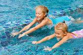 Dos niñas felices chapoteando en la piscina — Foto de Stock