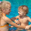 Little girl and little boy playing in the swimming  pool — Stock Photo