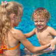 Stock Photo: Little girl and little boy playing in the swimming pool