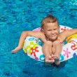 Stock Photo: Little girl in the pool with rubber ring
