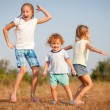 Two little girls and little boy dancing on the road — Stock Photo