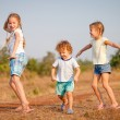 Two little girls and little boy dancing on the road — Stock Photo #27558299