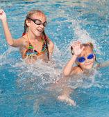 Dwie małe dziewczynki szczęśliwy popluskania się w basenie — Zdjęcie stockowe