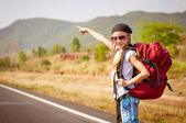 Little girl with backpack walking on the road — Stock Photo