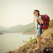 Little girl with backpack afternoon on the lake shore — Stock Photo