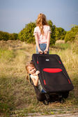 Two little girls with suitcase on the road — Stock Photo