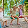 Stock Photo: Happy little girls and boy on a swing