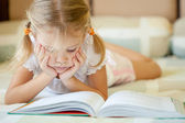 Little girl lying on the bed and reading a book — Stock Photo