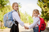 Two young little girls preparing to walk to school — Stock Photo