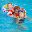 Happy little children playing in the swimming pool — Stock Photo