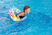 Little girl playing in the swimming pool — Stock Photo
