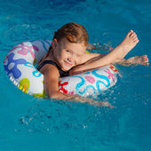 Little girl in the pool with rubber ring — Stock Photo