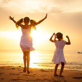 Happy children jumping on the beach on the dawn time — Stock Photo