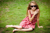 Beautiful little girl in sunglasses and a red dress — Stock Photo