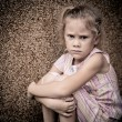 Portrait of a sad little girl sitting near the wall — Stock Photo