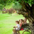 Happy kids sitting on the bench near the tree — Stock Photo