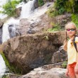 Happy little girl near the waterfall in the day time — Stock Photo