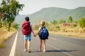 Two little girls with backpack walking on the road — Stock Photo