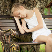 Portrait of a sad child sitting on a bench in the park under th — Stock Photo