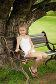 Happy girl sitting on the bench near the tree — Stock Photo