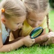 Two little girls with magnifying glass outdoors in the day time — Stock Photo