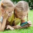 Two little girls with magnifying glass outdoors in day time — Stock Photo #32045895
