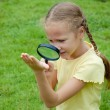 One little girl with magnifying glass outdoors in day time — Stock Photo #32046423