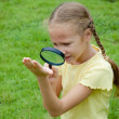 One little girl with magnifying glass outdoors in the day time — Stock Photo #32046423