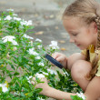 One little girl with magnifying glass outdoors in the day time — Foto de Stock