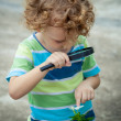 One little boy with magnifying glass outdoors in day time — Stock Photo #32046985