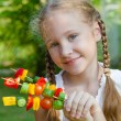 Girl holding a sticks  vegetables (cucumber, pepper, tomato) — Stock Photo