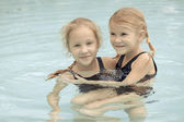 Two happy little girls playing around in the pool — Stock Photo