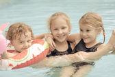 Dos niñas y niño jugando en la piscina — Foto de Stock
