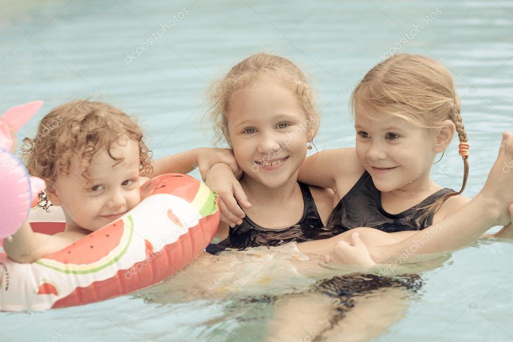 两个小女孩和小男孩在池中玩耍