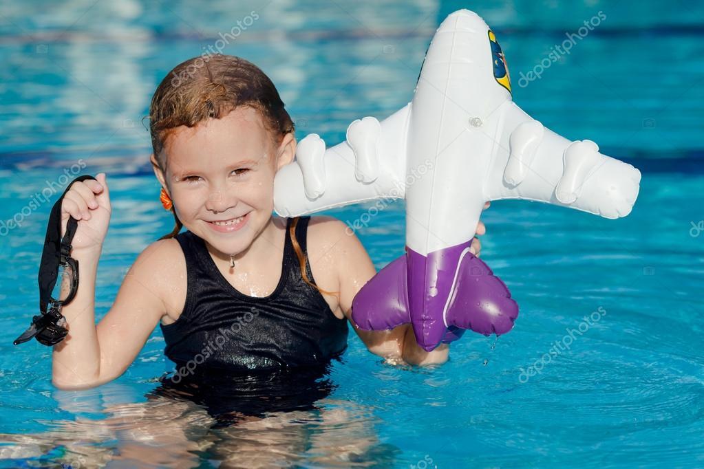 小女孩在游泳池里用充气玩具飞机