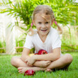 Little girl sitting on the grass and holding apples — Stock Photo