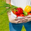 Womholding fresh vegetables in lap — Stock Photo #34126395