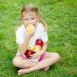 Little girl sitting on the grass and holding apples — Stock Photo #34126405