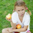Little girl sitting on the grass and holding apples — Stock Photo #34127509