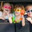 Two little girls  and boy sitting in the car  — Foto de Stock