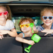 Two little girls and boy sitting in the car — Stock Photo #34129003