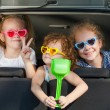 Two little girls and boy sitting in the car — Stock Photo #34129323