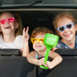 Two little girls and boy sitting in the car — Stock Photo #34129515