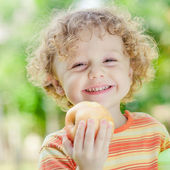 Little boy standing on the grass and holding apple — Stock Photo