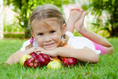 Little girl lying on the grass and holding apples — Stock Photo