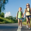 Two girls with backpacks walking on the road — Stock Photo